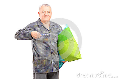 Mature man in pajamas holding a tooth brush and a pillow
