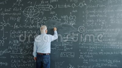 Mature man physicist writing formulas on blackboard with chalk indoors. At school busy with solving scientific problem. Science, occupation and education stock video footage
