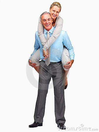 Mature man piggybacking his wife on a white