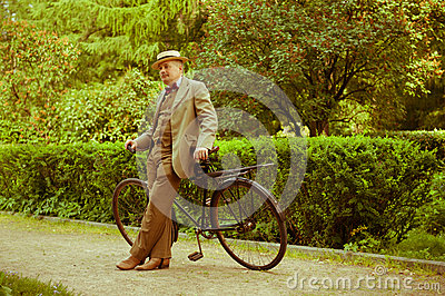 Mature man posing with retro bicycle in the park