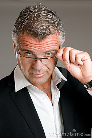 Mature man putting on glasses