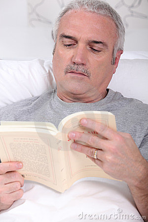 Mature man reading in bed