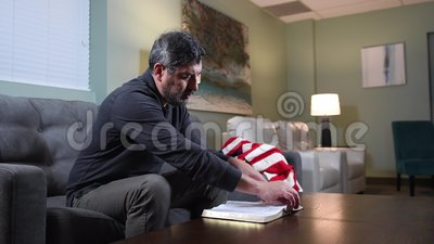Mature man reading the Bible at home. Mature man reading the Bible and praying at home seating on the couch stock video