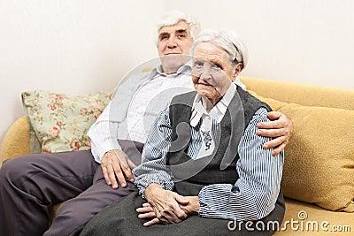 Mature man and senior woman sitting on sofa