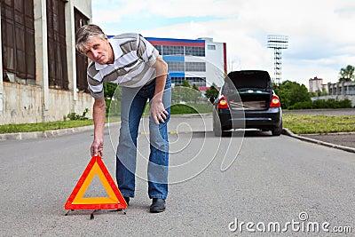Mature man sets triangle warning sign