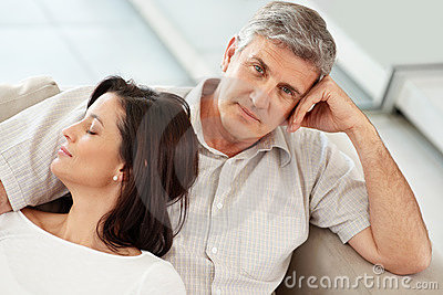 Mature man sitting with his wife sleeping on couch