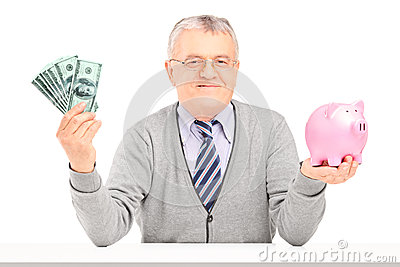 Mature man sitting, holding money and a piggy bank