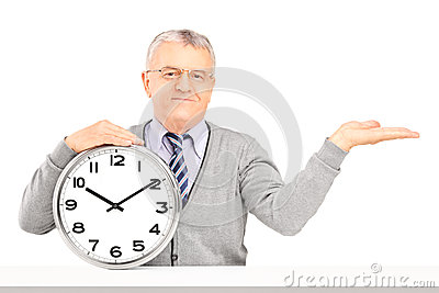 Mature man sitting and holding a wall clock
