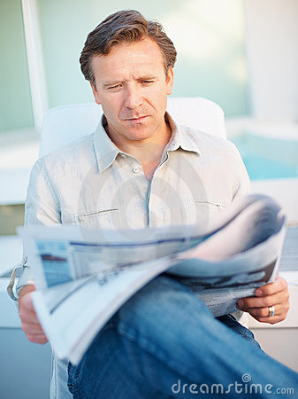 Mature man sitting and reading newspaper