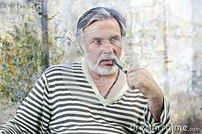 Mature man smoking tobacco pipe