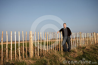 A mature  man standing against a fence
