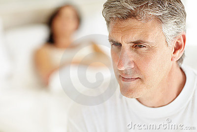 Mature man thinking with wife lying in bed at back