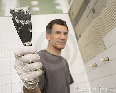Mature Man Tiling the Bathroom with Trowel