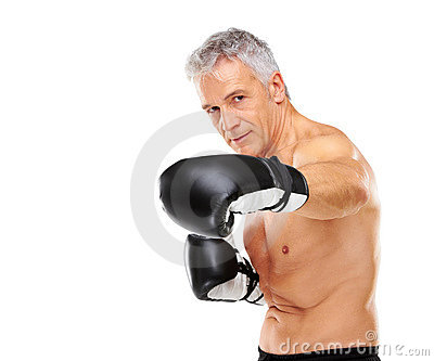 Mature man training with boxing gloves on white