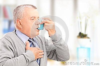 Mature man treating asthma with inhaler
