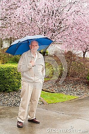 Mature Man with Umbrella in Rain