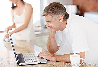 Mature man using a laptop with his wife