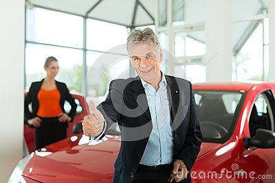 Mature man with woman and auto in car dealership