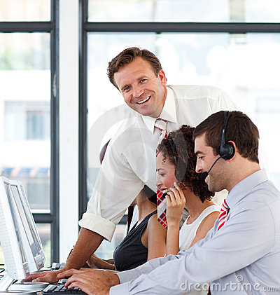 Mature manager in a call center smiling at the cam