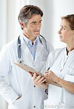 Mature medical staff making notes together