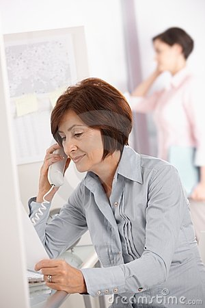 Mature office worker woman using landline phone