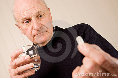 Mature older man holding tablet or pill with water