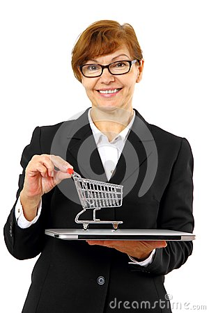 Mature red haired business woman with shopping cart, laptop