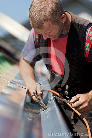 Mature roofer applying weld into the gutter