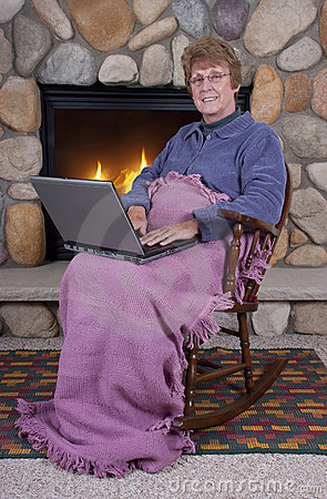 Mature Senior Woman Laptop Computer by Fireplace