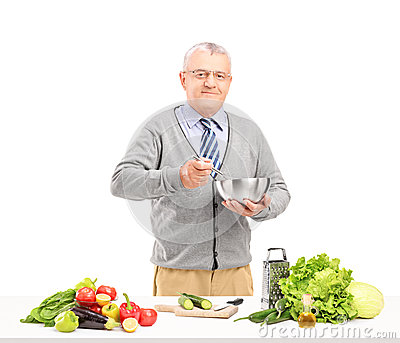 Mature smiling gentleman preparing a fresh salad