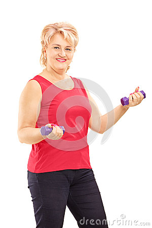 Mature smiling woman lifting up weights