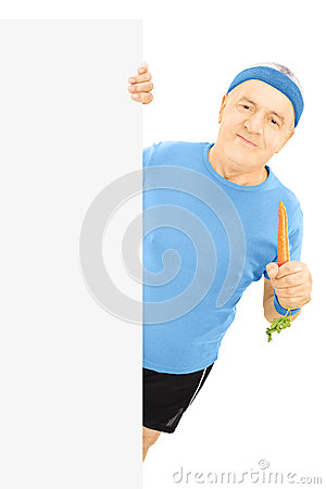 Mature sportsman holding a carrot and posing behind panel