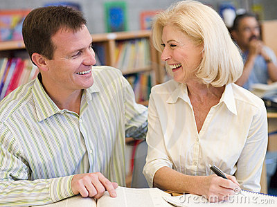 Mature student laughing with tutor in library