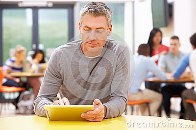 Mature Student Studying In Classroom With Digital Tablet