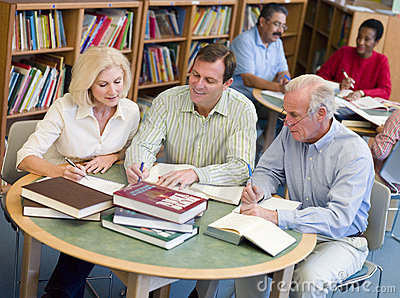 Mature students studying together in library