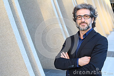 Mature urban business man with specs crossing his arms Stock Photo