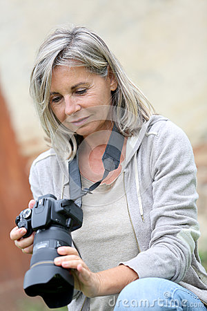 Mature woman checking pictures on screen camera