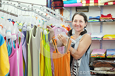 Mature woman  chooses dress at  shop