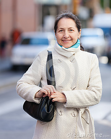 Mature woman at city street in autumn