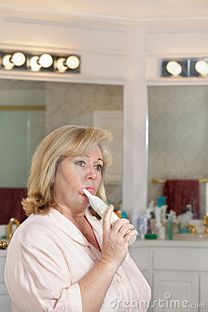 Mature woman cleaning teeth