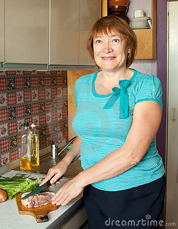 Mature woman is cooking meat