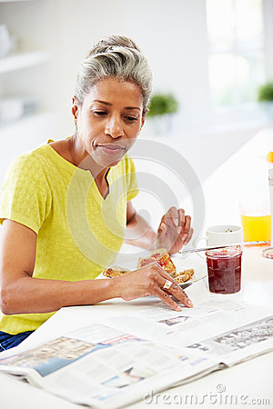 Free Mature Woman Eating Breakfast And Reading Newspaper Royalty Free Stock Photo - 35613085