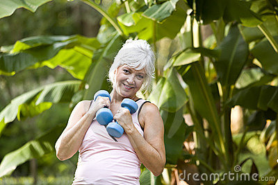 Mature woman exercising in park with hand weights
