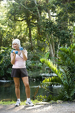 Mature woman exercising in park lifting hand weigh