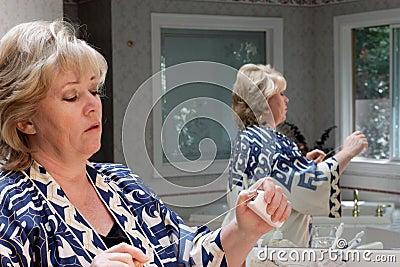 Mature woman flossing teeth