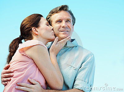 Mature woman giving a kiss to a man on his cheek