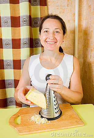 Mature woman grating cheese