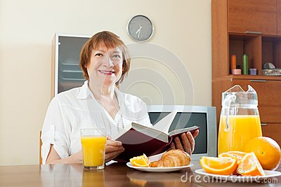 Mature  woman having breakfast with book