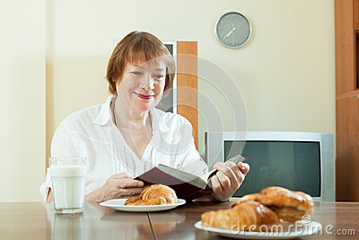 Mature  woman having breakfast with milk