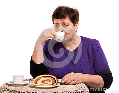 Mature woman having coffee with cake